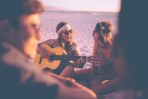 Girl playing guitar and singing for her friends at a summer evening beachparty