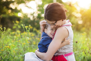 Happy young mother holding her son outside in summer nature