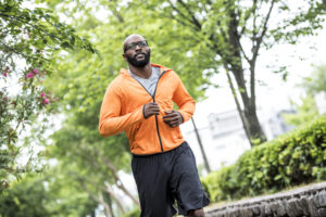 African american man running outdoors in the city. He is focused and determined.